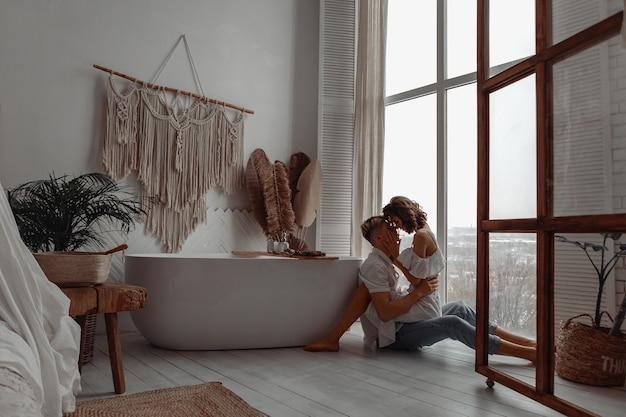 고급스러운 욕실 바닥에 앉아 사랑에 젊은 부부.