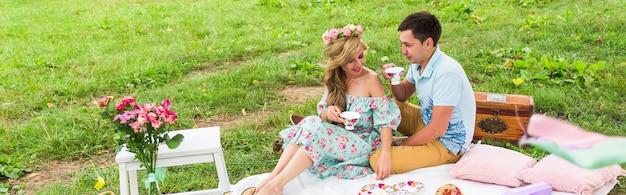 公園の格子縞のピクニックに座って、お茶を飲み、自然の中で一日を楽しんでいる愛の若いカップル。
