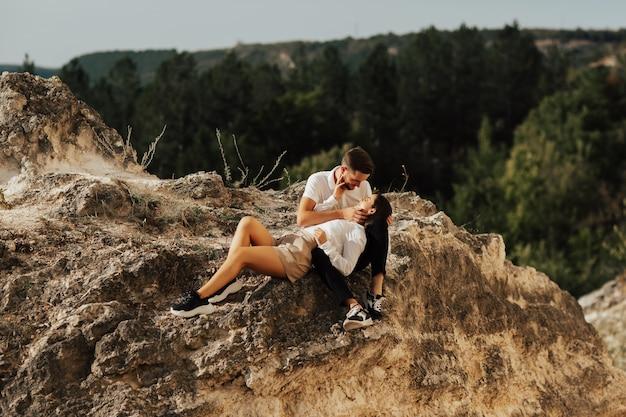 Молодая влюбленная пара сидит на камне с видом на горы и смотрит друг на друга