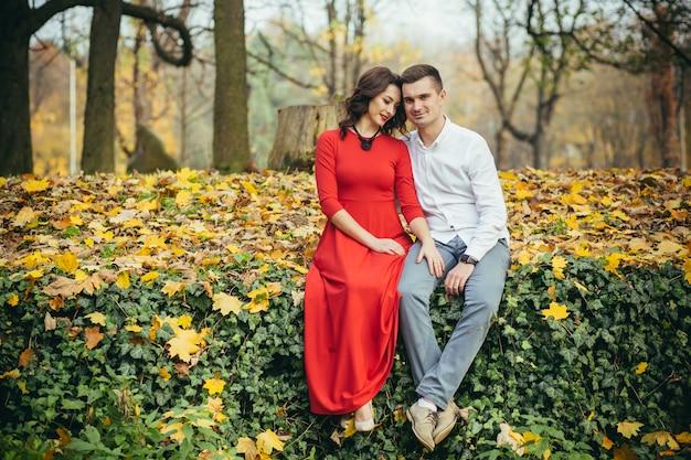 Молодая влюбленная пара, сидя на осеннем листе в парке.