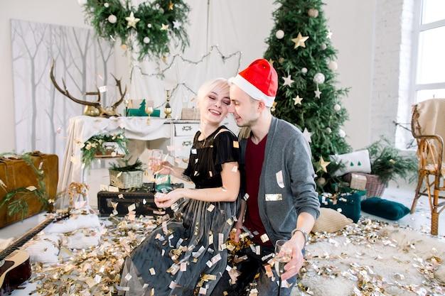 黄金の紙吹雪を投げてクリスマスツリーの近くの床に座って恋に若いカップル