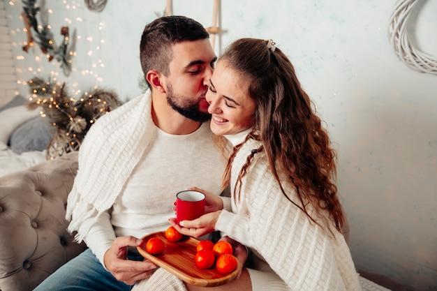 Молодая влюбленная пара сидит на диване и целуется, держа чашку чая в рождественской обстановке