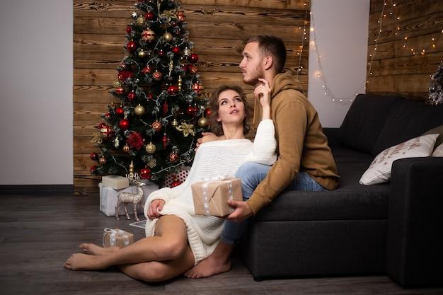 배경에 크리스마스 트리에 집에서 소파에 앉아 사랑에 젊은 부부