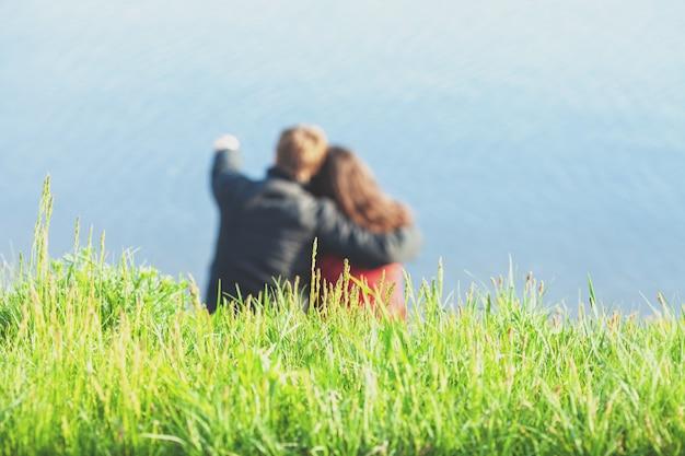 ビーチに座って海を見ている愛の若いカップル選択的な焦点