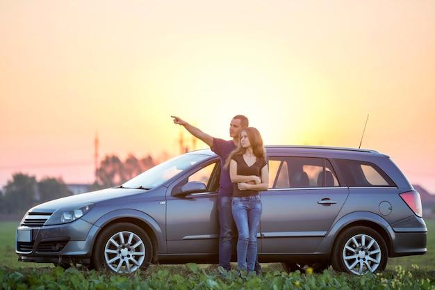 若いカップルの愛、スリムな魅力的な長い髪の女性とハンサムな男が緑の野原で銀の車で距離立ってを指しています。
