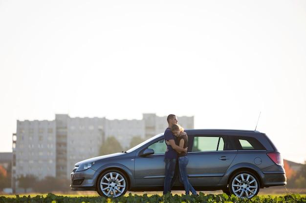 愛の若いカップル、長いポニーテールとハンサムな男がぼやけたアパートの建物と澄んだ空のコピースペースの背景に緑の野原で銀の車に一緒に立っているスリムな魅力的な女性。