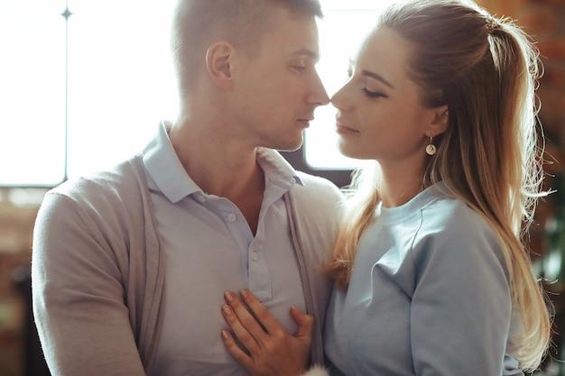 一緒に時間を過ごすのが大好きな若いカップル。家で親密な瞬間を持っている美しい女性とハンサムな男