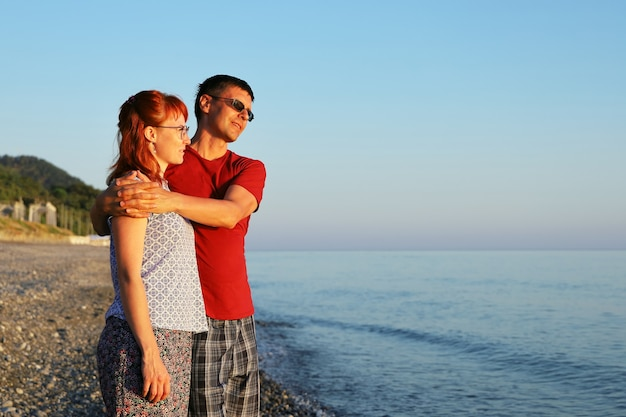 恋に落ちた若いカップルが海岸に立って夕日を眺める