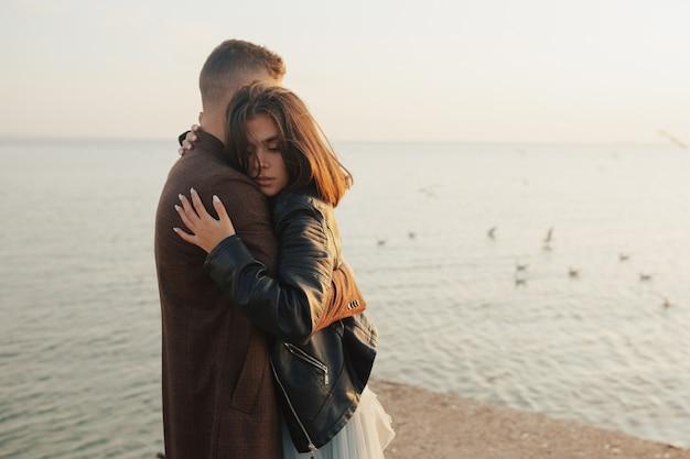 海辺のビーチに立って、情熱を持って抱きしめる愛の若いカップル。