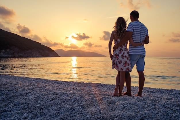Молодая пара в любви, стоя на пляже на берегу моря, наслаждаясь романтическим вечером и наблюдая закат. семья отдыхает летом на пляже.