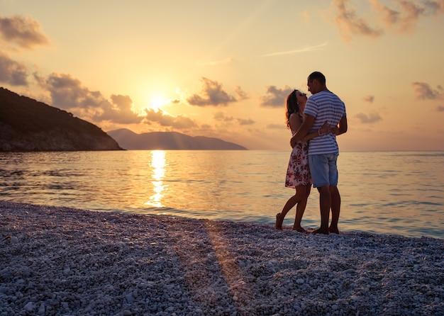 Молодая пара в любви, стоя на пляже на берегу моря, наслаждаясь романтическим вечером и наблюдая закат.