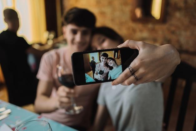 그들의 날짜에 셀카를 복용 사랑에 젊은 부부-젊은 부부는 레스토랑에 앉아.