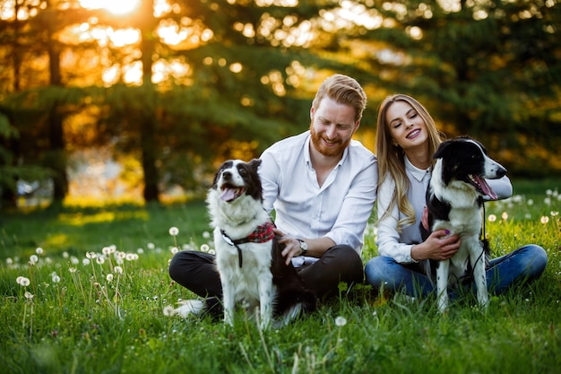 Молодая пара в любви гуляет и наслаждается временем в парке с собаками. концепция усыновления собачьих людей