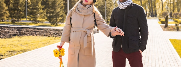 手をつないで秋の公園を歩く愛の若いカップル。