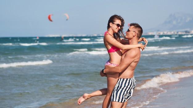 ビーチの上を歩く愛の若いカップル。