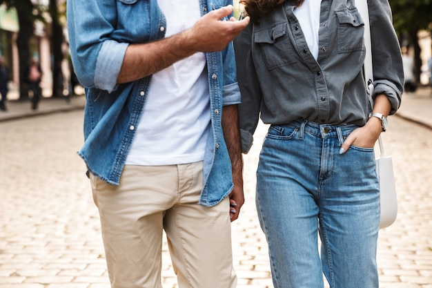 街の通りで屋外を歩く愛の若いカップル