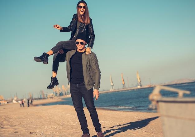 Молодая влюбленная пара гуляет по морю. весна осень. парень одет в куртку и шляпу. девушка в шляпе и кожаной куртке с шарфом и очками