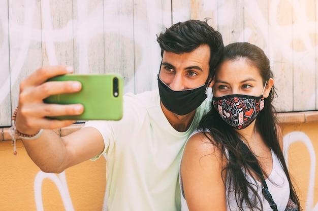 フェイスマスクを身に着けている愛の若いカップルは携帯電話で自分撮りを取りますコピースペース