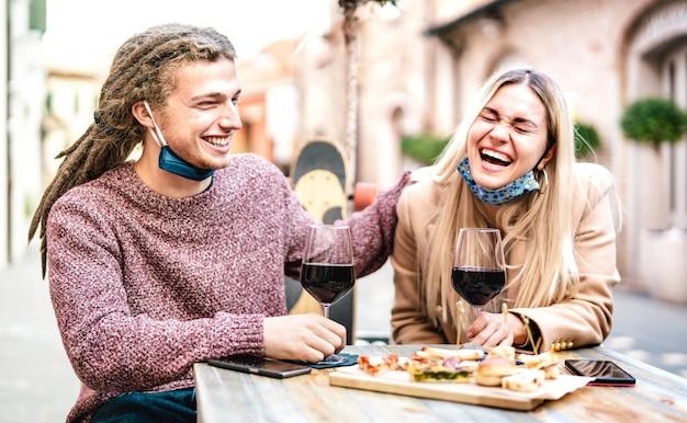 外のワインバーで楽しんでオープンフェイスマスクを身に着けている愛の若いカップル