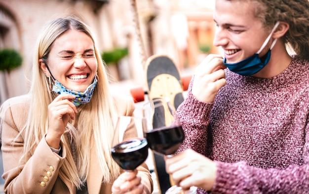 オープンフェイスマスクを着用し、屋外のワイナリーバーで楽しんでいる愛の若いカップル-左の女性に焦点を当てる