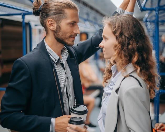 地下鉄の車内に立っているテイクアウト コーヒーに恋する若いカップル