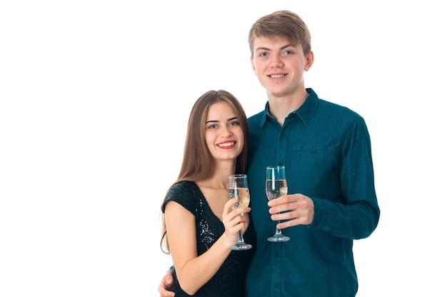 Молодая влюбленная пара с двумя бокалами шампанского в студии на белом фоне