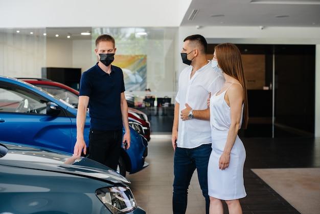 マスクをした若いカップルが新しい車を選び、ディーラーの代表者に相談するi