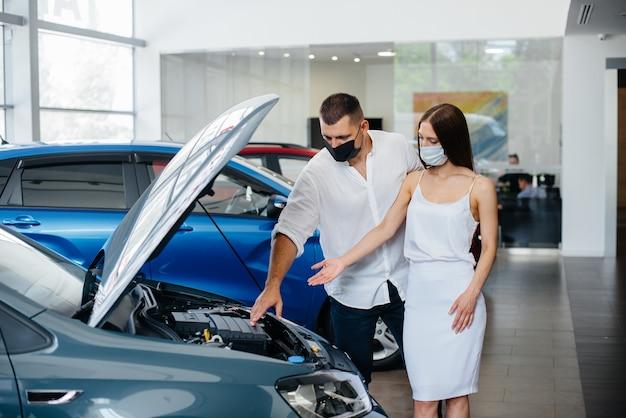 仮面をかぶった若いカップルが新しい車を選び、パンデミックの時期にディーラーの担当者に相談します。車の販売、パンデミック時の生活。