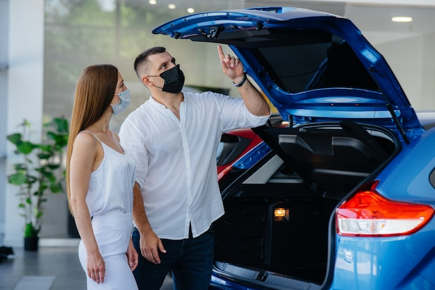 仮面をかぶった若いカップルが新しい車を選び、パンデミックの時期に販売店の担当者に相談します。車の販売、パンデミック時の生活。