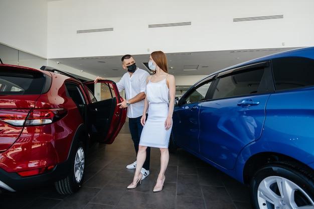 仮面をかぶった若いカップルが新しい車を選び、パンデミックの時期に販売店の担当者に相談します。