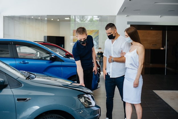 Молодая пара в масках выбирает новый автомобиль и консультируется с представителем автосалона в период пандемии.
