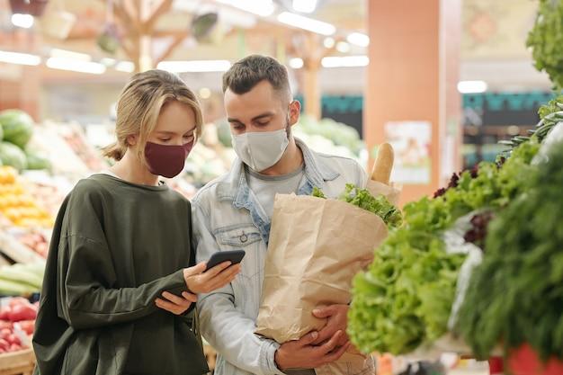 Молодая пара в масках стоит у прилавка и вместе проверяет фрукты перед покупкой