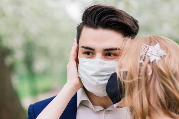 公園の医療マスクの若いカップル