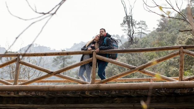 橋の上に座って自然の中で若いカップル