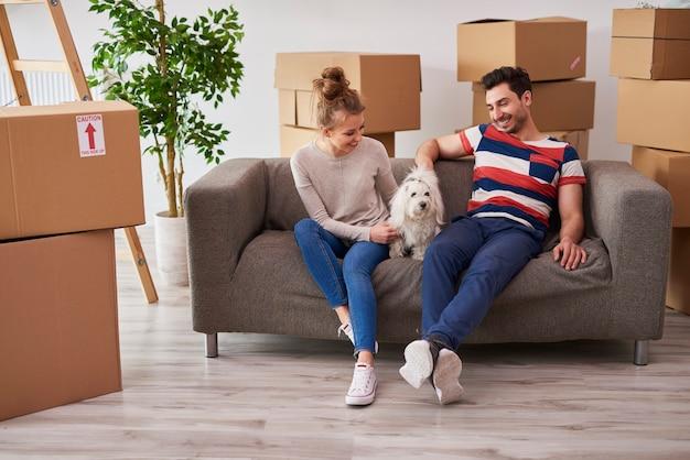 Молодая пара в новой квартире с маленькой собакой
