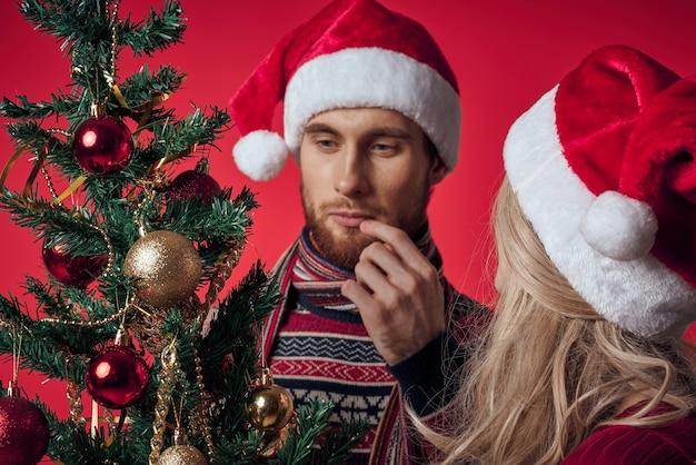 新年の服の若いカップルのクリスマスツリーの装飾の休日の楽しみ。高品質の写真