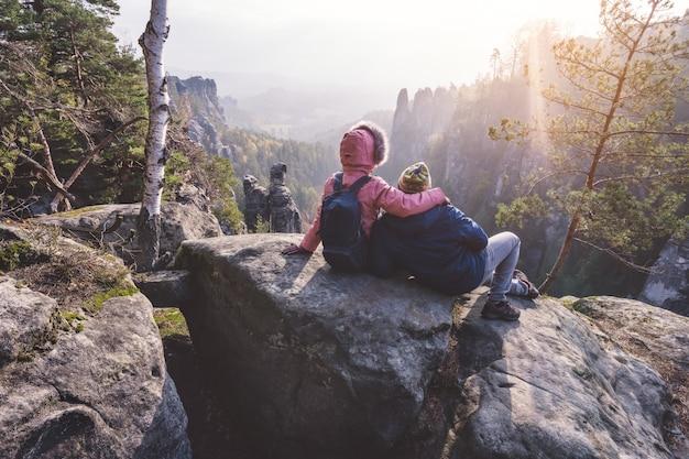 Молодая пара в верхней одежде с рюкзаками отдыхает после похода на известняковую скалу