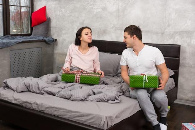 クリスマスの朝にロフトスタイルで寝室のベッドに座っている間、パジャマの若いカップルはお互いのプレゼントを検討します