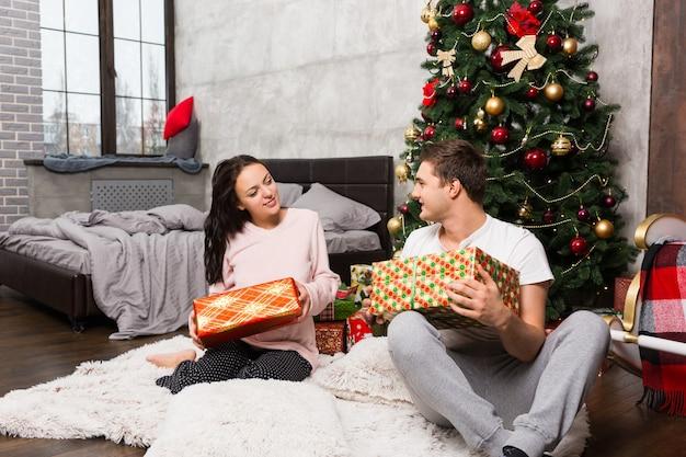 パジャマ姿の若いカップルは、ロフトスタイルの部屋のクリスマスツリーの近くのカーペットに座ってプレゼントを喜んでいます