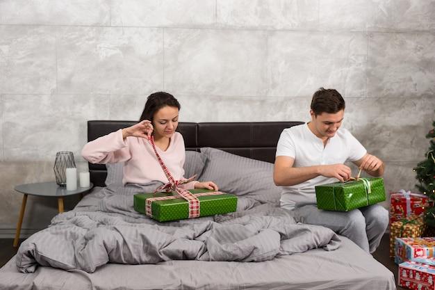 クリスマスの朝にロフトスタイルで寝室のベッドに座ってプレゼントを開梱するパジャマを着た若いカップル