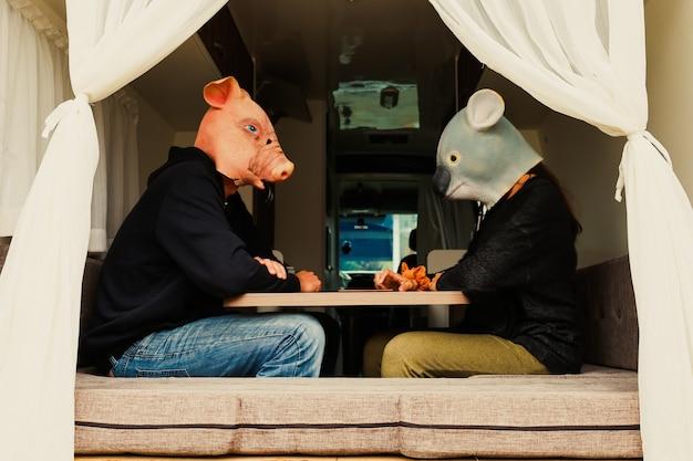 Молодая пара в маске свиньи и коалы, путешествующей на автомобиле