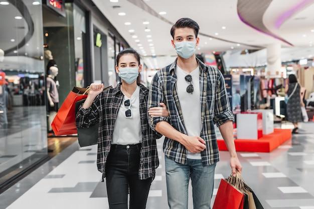 Молодая пара в защитной маске, держащая несколько бумажных пакетов для покупок, гуляет по коридору большого торгового центра