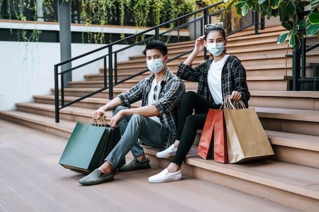 複数の紙の買い物袋を保持している保護マスクの若いカップル