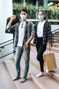 여러 종이 쇼핑백을 들고 보호 마스크에 젊은 부부