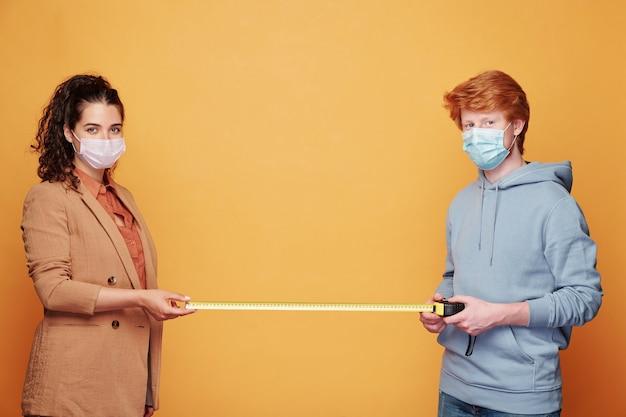 Молодая пара в защитных масках размером два метра между ними, стоя у желтой стены перед камерой