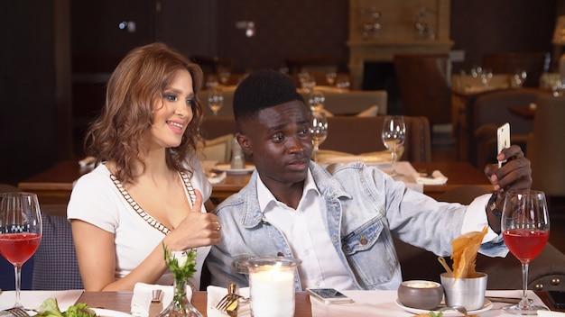 スマートフォンでselfieを作るレストランで若いカップル。