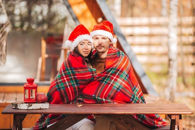 Молодая пара в шляпе санта, сидя на открытом воздухе осенью