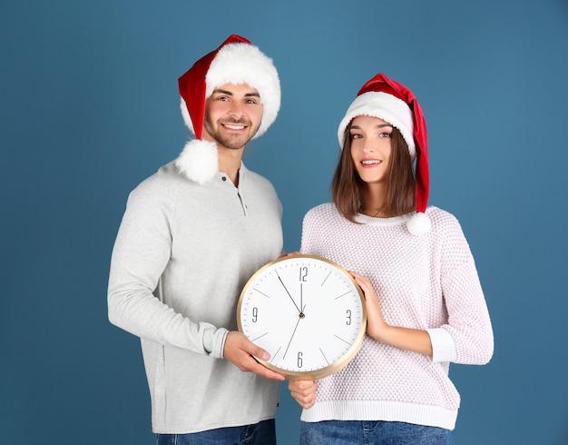 색상 배경에 시계와 산타 모자에 젊은 부부
