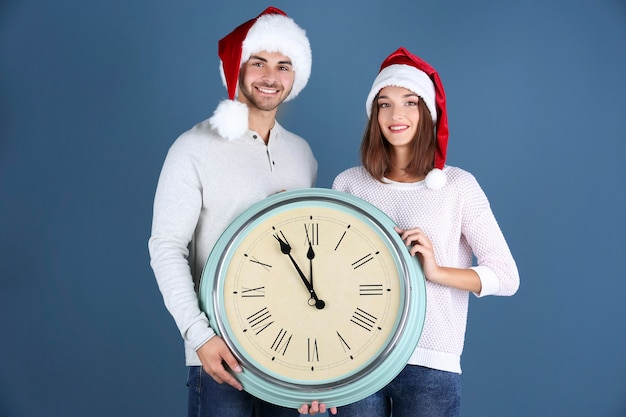 색상 공간에 시계와 산타 모자에 젊은 부부. 크리스마스 카운트 다운 개념