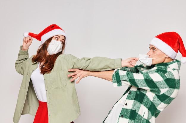 サンタの帽子の若いカップルの感情楽しいスタジオ灰色の背景